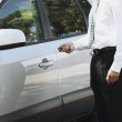 Hispanic businessmunlocking car — Stock Photo #23275868