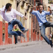 Hispanic men kicking heels in air — Stock Photo