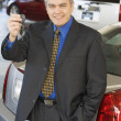 Hispanic car salesman holding car keys — Stock Photo