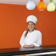 Hispanic female baker in gourmet food store — Stock Photo