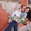 Hispanic couple hugging with roses — Lizenzfreies Foto