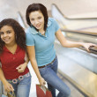 Multi-ethnic teenage girls riding escalator in mall — Stock Photo