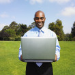 African businessman holding laptop in field — Stock fotografie