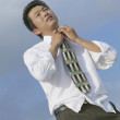 Asian businessman adjusting necktie — Stock Photo