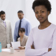 African businesswoman with co-workers in background — Stock Photo