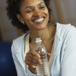African woman drinking from water bottle — Foto Stock