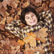 Mixed Race boy laying in autumn leaves — Stock Photo