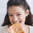 Hispanic girl eating pizza — Stock Photo