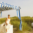 Bride under tent at beach — Stock Photo
