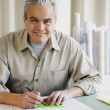 Hispanic male architect writing at desk — Stock Photo