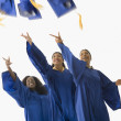Multi-ethnic female graduates throwing caps in air — Stock Photo #23276332