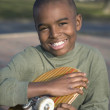 Stock Photo: African boy holding skateboard