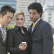 Three businesspeople looking at cell phone — Stock Photo #23276514