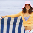 Woman leaning on sun shade at beach — Stock Photo