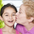 Hispanic grandmother kissing granddaughter on cheek — Stock Photo