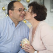 Hispanic woman kissing husband on Christmas — Foto de Stock