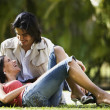 South American couple sitting on grass — Stock Photo