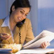 Hispanic businesswoman reading newspaper — Stock Photo