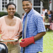 African couple cooking on barbeque grill — Stock Photo