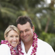 Couple wearing bathrobes and leis — Stock Photo