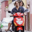 Hispanic couple on scooter - Stockfoto