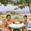 Young couple eating at beach resort — Stock Photo
