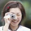 Asian woman taking photograph — Stock Photo