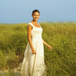 Bride standing in dune grass — Stock Photo