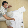 Man on floor with blueprints — Stock Photo