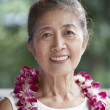 Senior Asian woman wearing lei — Stock Photo
