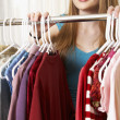 Stock Photo: Hispanic womnext to rack of clothing