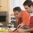 Two middle-aged men cooking - Stock Photo