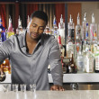 Stock Photo: Africmale bartender making drinks