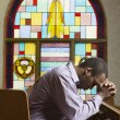 African American man praying in church - Stock fotografie