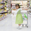 Hispanic girl pushing child's shopping cart — Stock Photo #23277418
