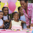 African girl and cake at birthday party — Stock Photo