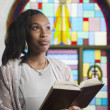 African American woman reading Bible in church - Stock fotografie