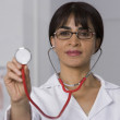 Стоковое фото: Female doctor holding up stethoscope
