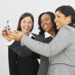 Multi-ethnic businesswomen looking at cell phone — Stock Photo #23277524