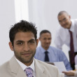 Indian businessman with co-workers in background — Stock Photo