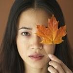 asiatique femme tenant la feuille d'automne sur œil — Photo