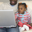 African father and daughter looking at laptop — Stock Photo