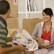 Stock Photo: Young couple packing moving boxes