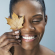 African woman holding autumn leaf over eye — Stock Photo