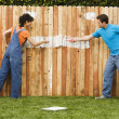 Multi-ethnic couple painting fence — Stok fotoğraf