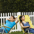 Multi-ethnic couple relaxing in lawn chairs — Stock Photo