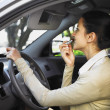 Stock Photo: Hispanic womapplying lipstick in car
