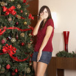 Hispanic woman laughing next to Christmas tree — Stock Photo