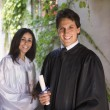 Stock Photo: Graduating mand womholding diplomas