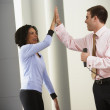 Businessman and businesswoman high-fiving — Stock Photo #23278096